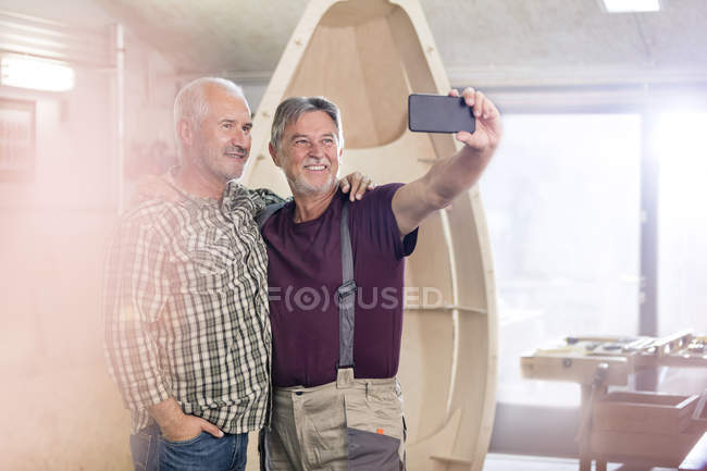 Proud, smiling male carpenters with camera phone taking selfie next too wood boat in workshop — Stock Photo