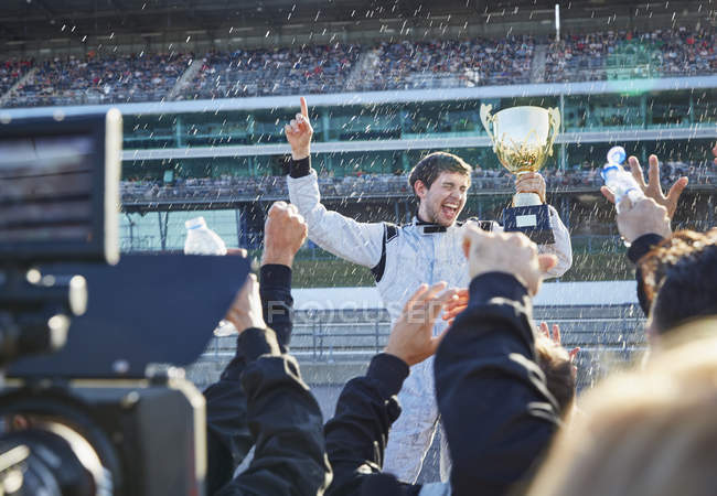 Formula one racing team spraying champagne on driver with trophy, celebrating victory on sports track — стокове фото