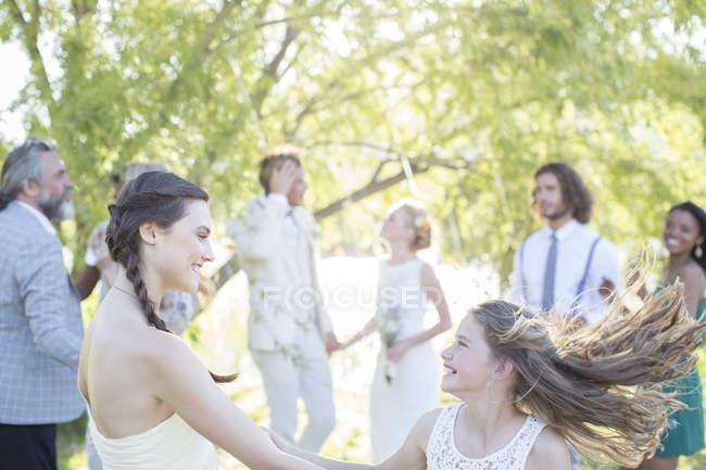 Подружка невесты и девушка танцуют во время свадебного приема в домашнем саду — стоковое фото