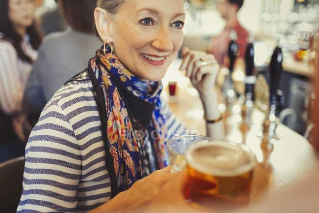 Senior mulher bebendo cerveja no bar — Fotografia de Stock