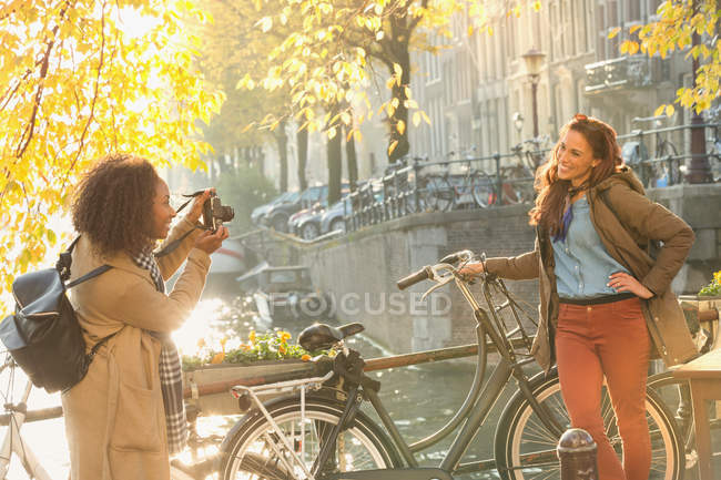 Young woman photographing friend with bicycle along autumn canal, Amsterdam — Stock Photo