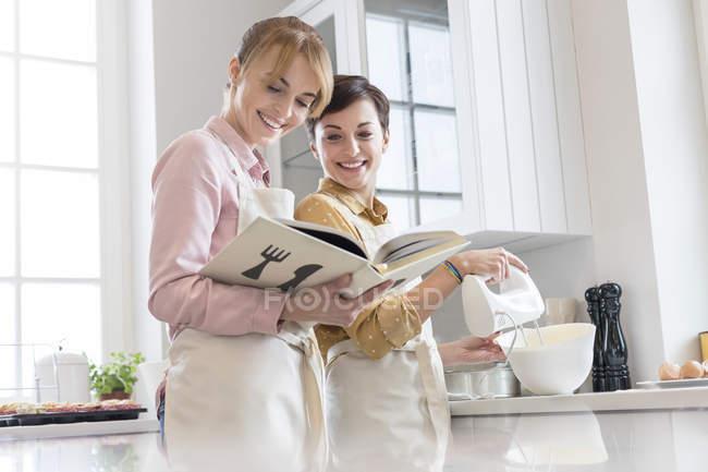 Caterers femelles avec livre de cuisine cuisson dans la cuisine, à l'aide d'un mélangeur électrique à main — Photo de stock