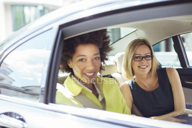 Бізнес-леді посміхаючись у спині сидінні автомобіля — стокове фото