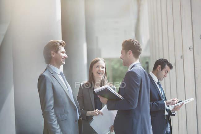 Uomini d'affari che parlano e ridono nella soleggiata hall dell'ufficio — Foto stock