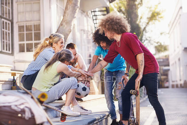 Друзі з футбольним м'ячем і скейтбордах, торкаючись руки в туляться на міських кроки — стокове фото