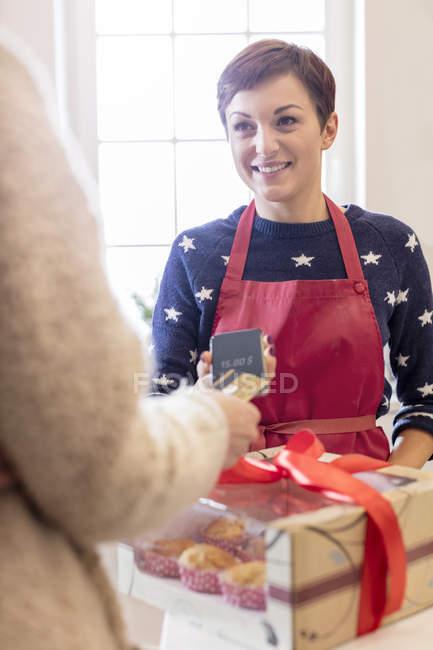Traiteur femme vente boîte de pâtisseries cuites à la femme en utilisant un lecteur de carte de crédit téléphone intelligent — Photo de stock
