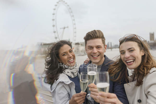 Portrait enthusiastic, smiling friends celebrating, toasting champagne near Millennium Wheel, London, UK — Stock Photo