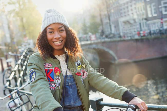 Retrato sorridente jovem ao longo do canal urbano, Amsterdã — Fotografia de Stock