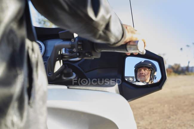 Blick auf älteren Mann im Seitenspiegel Motorrad fahren — Stockfoto