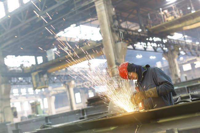 Welder using welding torch in steel factory — Stock Photo