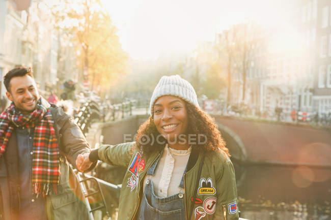 Portrait jeune couple souriant tenant la main le long du canal à Amsterdam — Photo de stock