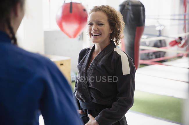 Lächelnde Frauen üben Judo in Turnhalle — Stockfoto