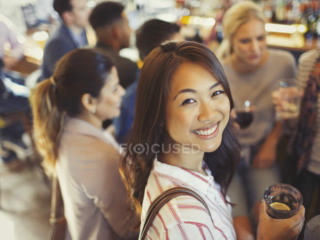 Portrait smiling woman drinking with friends at bar — Stock Photo