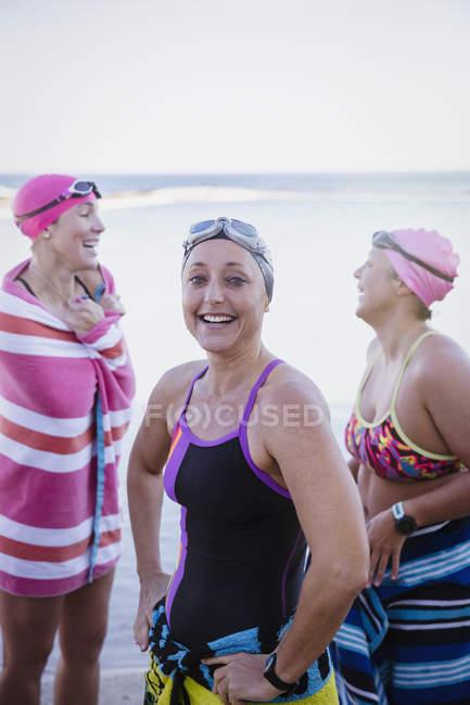 Sorridente nuotatori femminili con asciugamani in mare aperto — Foto stock