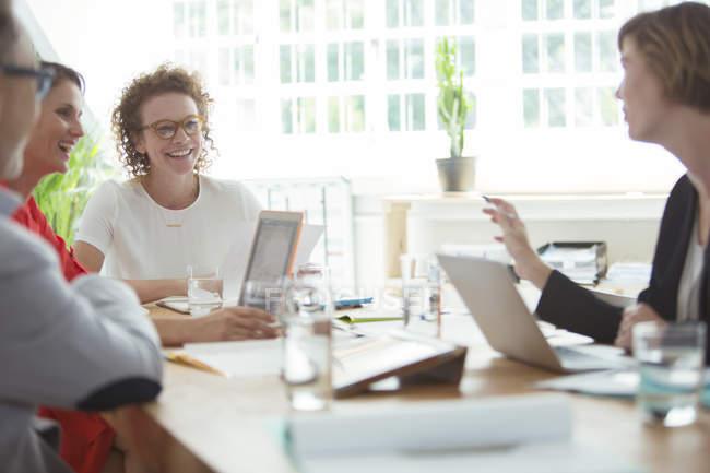 Люди разговаривают и улыбаются во время деловой встречи в офисе — стоковое фото