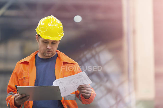 Steel worker reviewing blueprints in factory — Stock Photo
