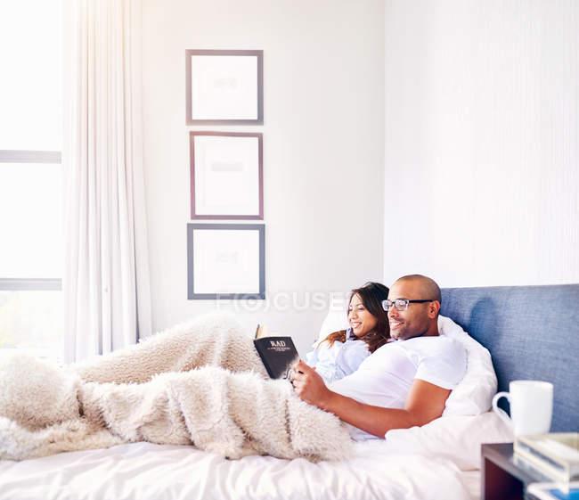 Sonriente pareja relajante, lectura libro en la cama - foto de stock