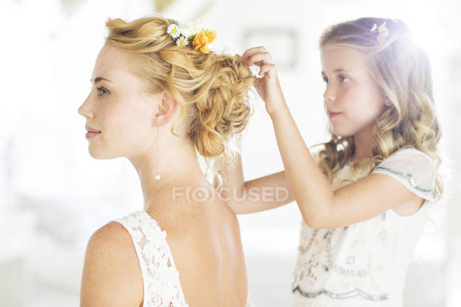 Bridesmaid helping bride with hairstyle in domestic room — Stock Photo