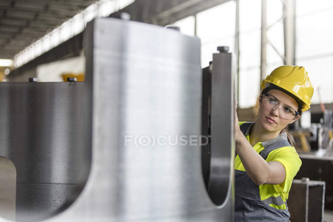 Female steel worker examining steel part in factory — Stock Photo