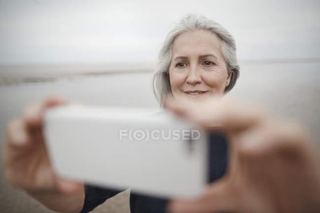 Senior woman taking selfie with camera phone on winter beach — Stock Photo
