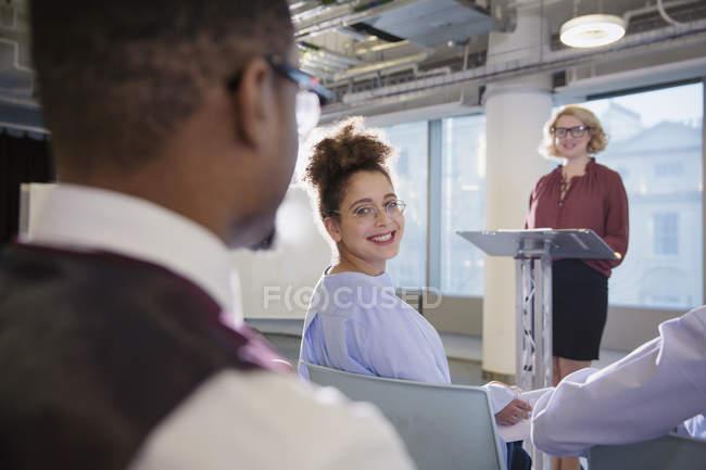 Lächelnd Geschäftsfrauen drehen und Geschäftsmann in Zielgruppe Konferenz anhören — Stockfoto