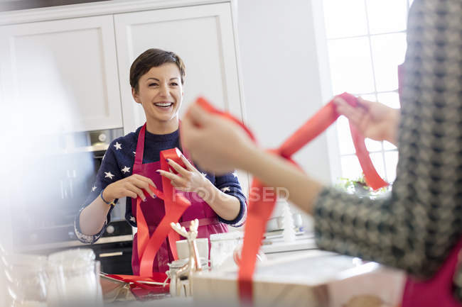 Traiteuses souriantes enveloppant les produits de boulangerie dans des boîtes avec ruban rouge dans la cuisine — Photo de stock