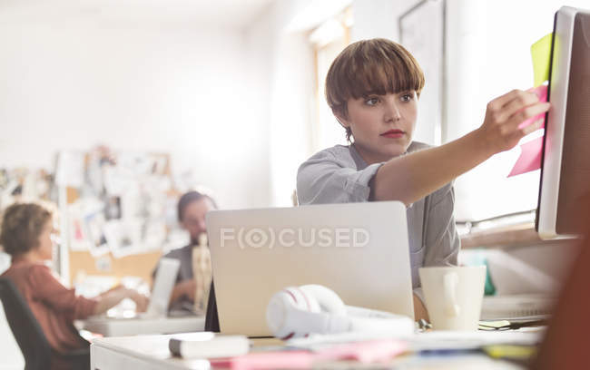 Serious female designer reviewing adhesive notes on computer in office — Stock Photo
