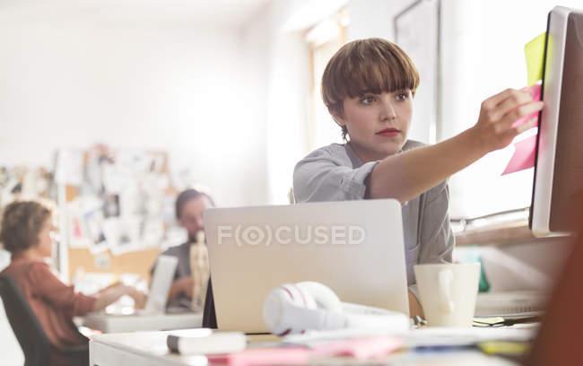 Серйозні жіночий дизайнер рецензування клей нотатки на комп'ютері в офісі — стокове фото