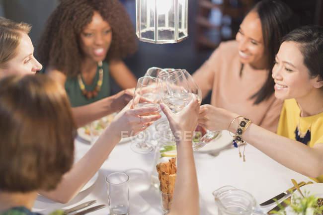 Mulheres sorridentes amigos brindar copos de vinho branco jantar na mesa do restaurante — Fotografia de Stock