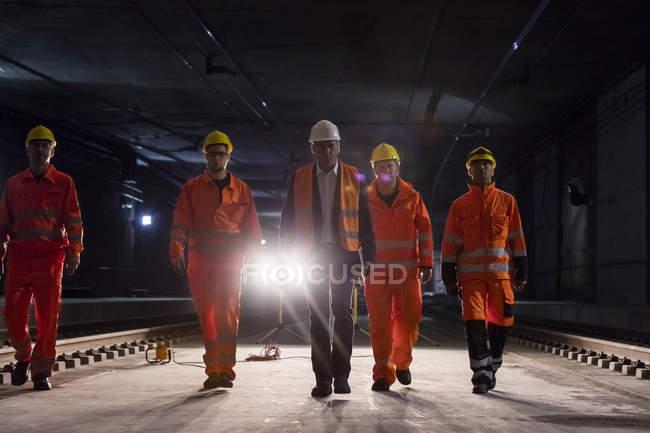 Мужчина бригадир и строители идут по темной строительной площадке под землей — стоковое фото