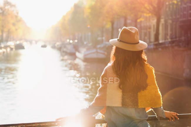 Femme regardant la vue ensoleillée sur le canal d'automne, Amsterdam — Photo de stock