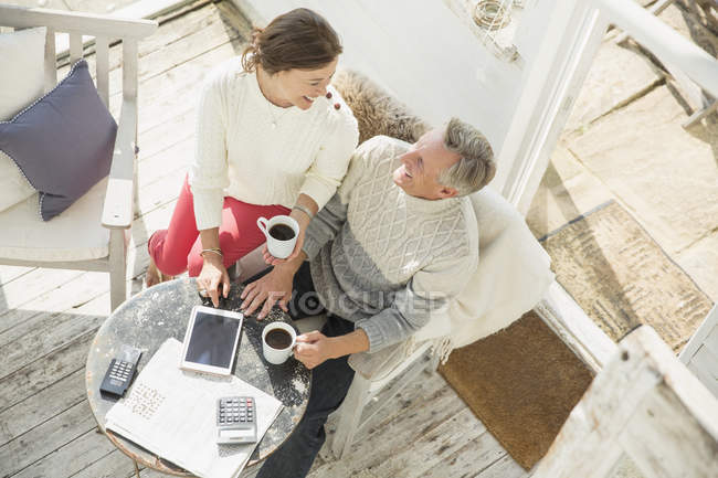 View from above mature couple drinking coffee and using digital tablet on sun porch — стоковое фото
