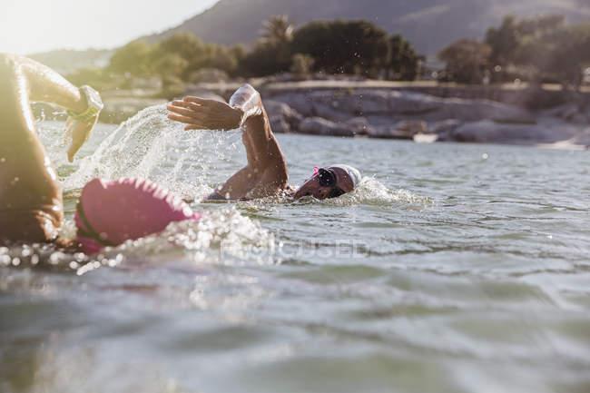 Femininos nadadores ativos no oceano contra costa durante o dia — Fotografia de Stock