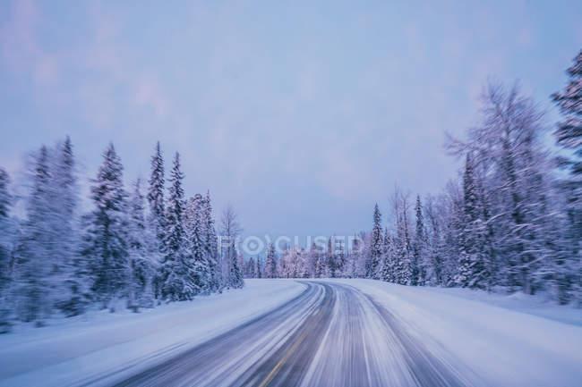 Strada di inverno remoto attraverso neve coperto foresta gli alberi contro il cielo blu, Lapponia, Finlandia — Foto stock