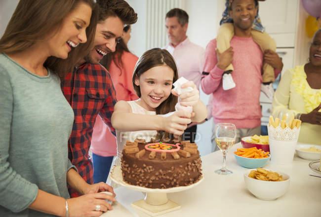 Усміхнене сім'ї обмерзання шоколадний торт в кухні — стокове фото