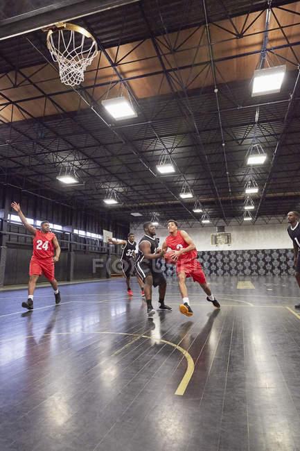 Молодые баскетболисты играют в баскетбол на площадке в гимназии — стоковое фото