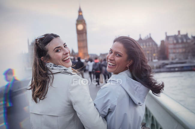 Portrait, sourire, amis enthousiastes de femmes marchant sur le pont en direction de Big Ben, London, Uk — Photo de stock