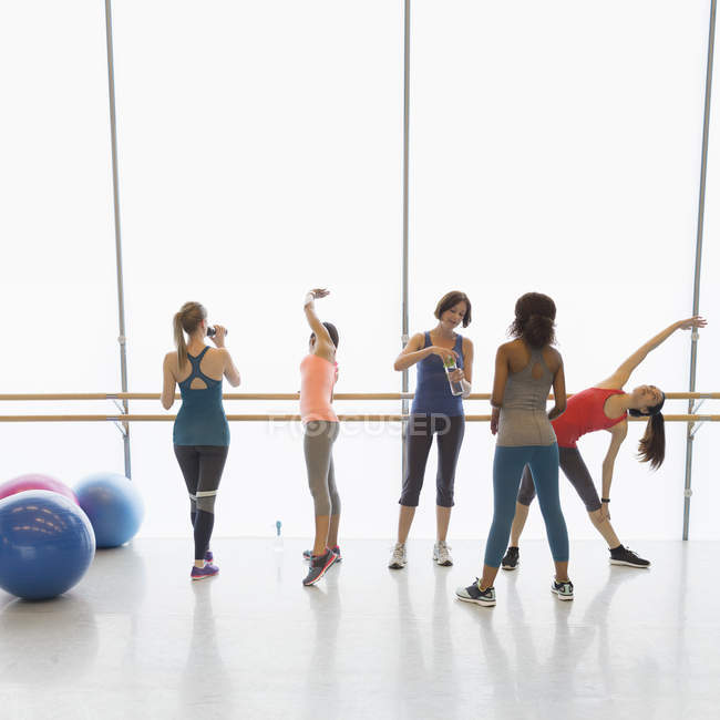 Women stretching and drinking water in exercise class gym studio — Stock Photo