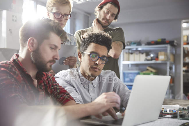 Serious, focused designers working at laptop in workshop — Stock Photo