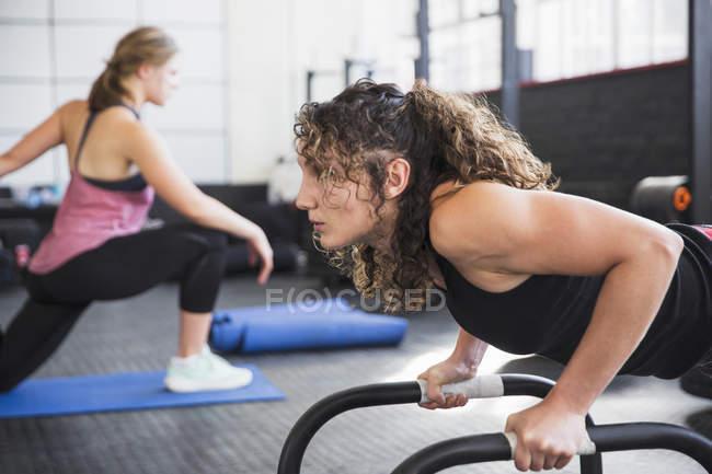 Entschlossene junge Frau macht Liegestütze mit Geräten im Fitness-Studio — Stockfoto