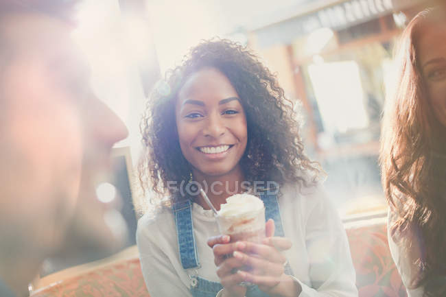 Portrait smiling young woman drinking milkshake with friends in cafe — Stock Photo