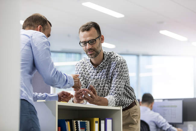 Businessmen using cell phone in office — Stock Photo