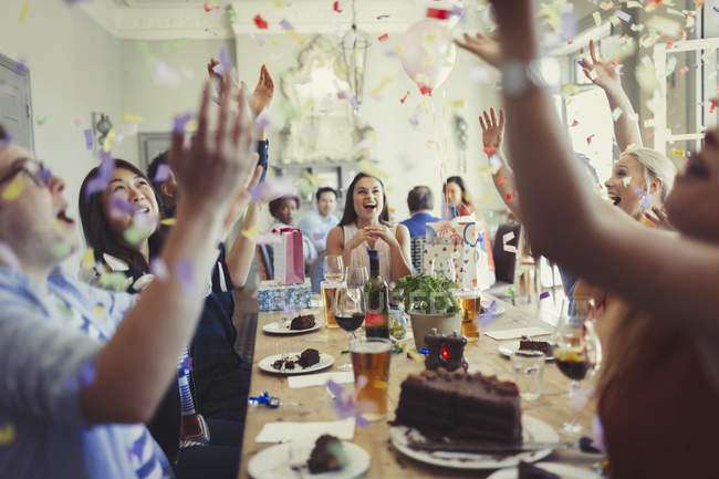 Friends celebrating birthday throwing confetti overhead at restaurant table — Stock Photo