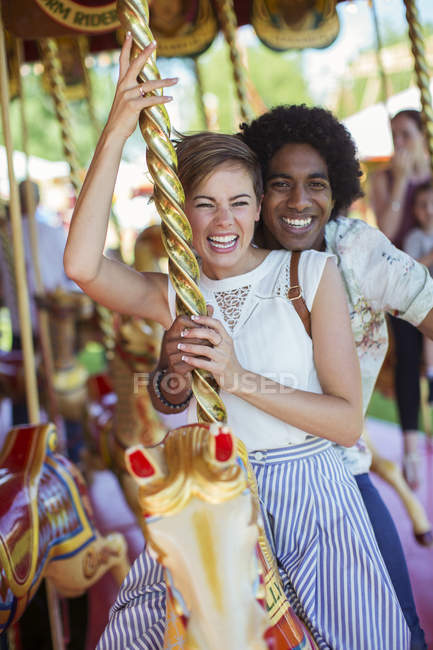 Young multiracial couple smiling on carousel in amusement park — Stock Photo