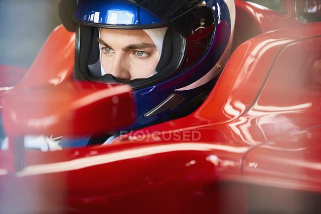 Крупный план Формулы-1 водитель в шлеме в гоночной машине — стоковое фото