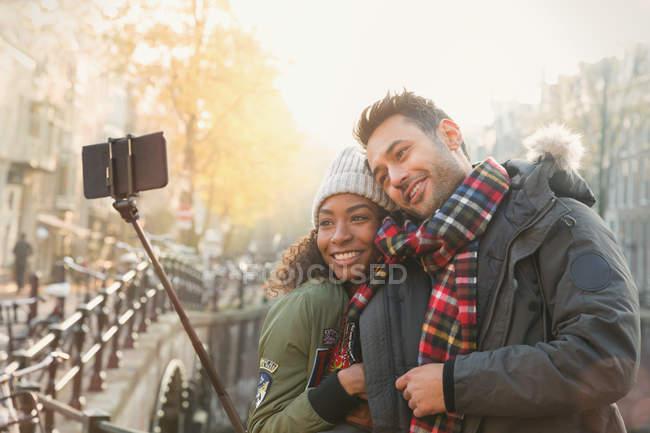 Casal afetuoso abraçando e tirando selfie com vara selfie na ponte de outono, Amsterdam — Fotografia de Stock