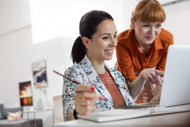 Усміхнених жінок, що працюють на ноутбук — стокове фото
