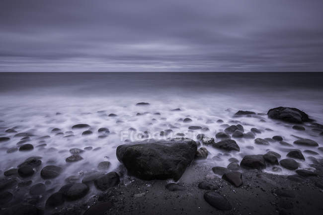 Tranquil overcast gray seascape and rocks on beach, Kalundborg, Denmark — Stock Photo