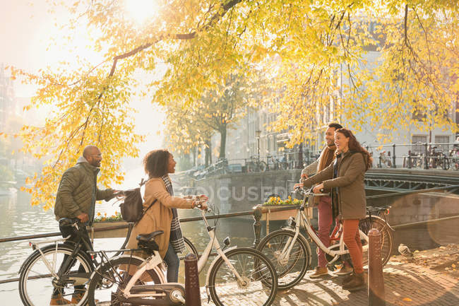 Друзья на велосипедах вдоль солнечного осеннего канала в Амстердаме — стоковое фото