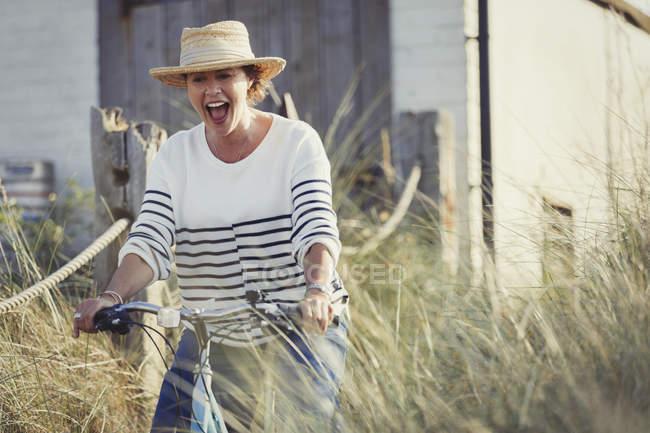 Spielerische Reife Frau reiten Fahrrad auf Strandhafer Weg — Stockfoto
